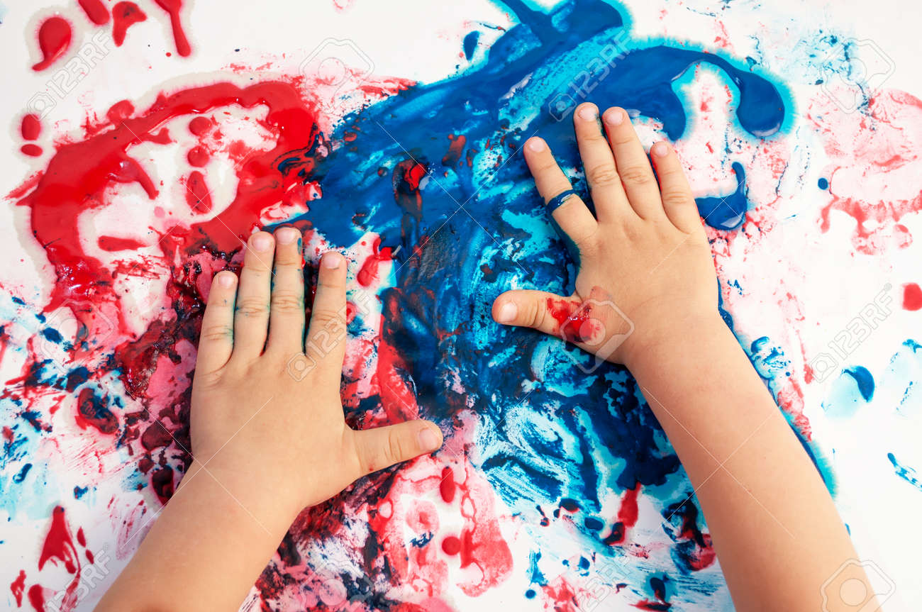 Painted hands smudging colors on messy paper . - 103156639