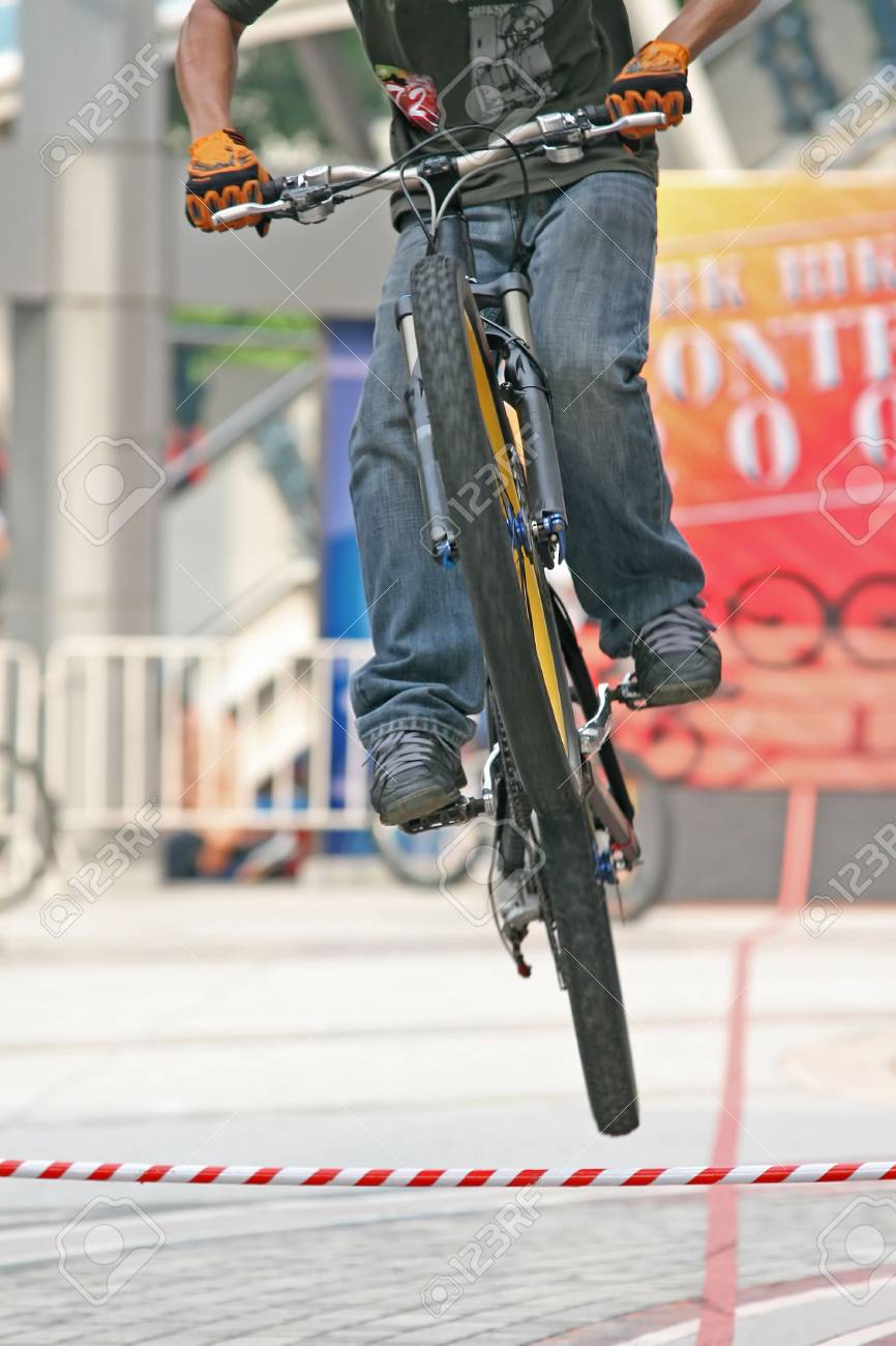 Young guy on a mountain bike performs a jump during a competition Stock Photo - 929562