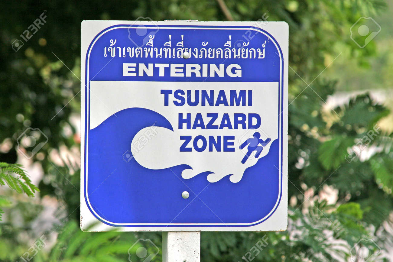 A tsunami warning sign located near a beach in Phuket, Thailand