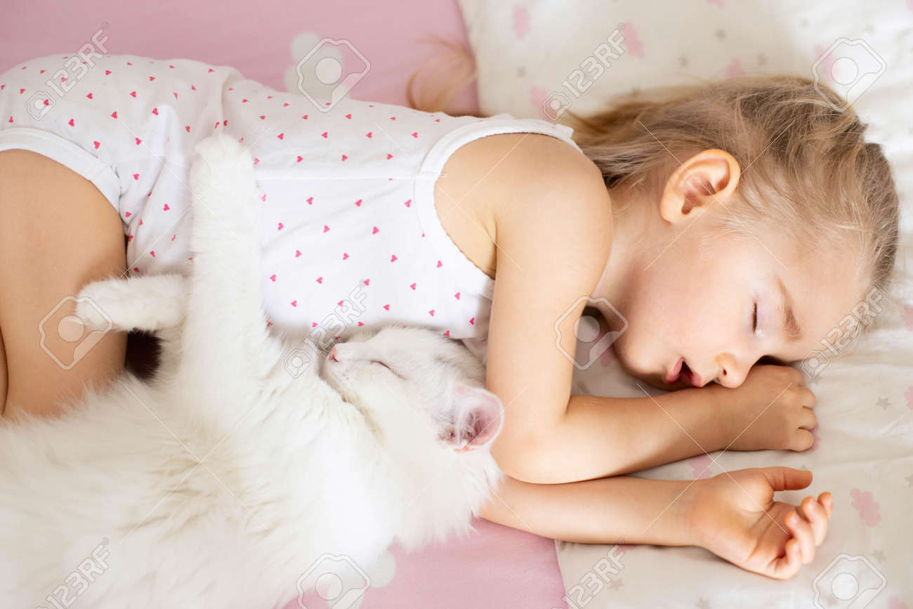 A little girl sleeps in a crib with pink bed linen with clouds, a white cat in the nursery. Quiet hour, top view. - 167408261