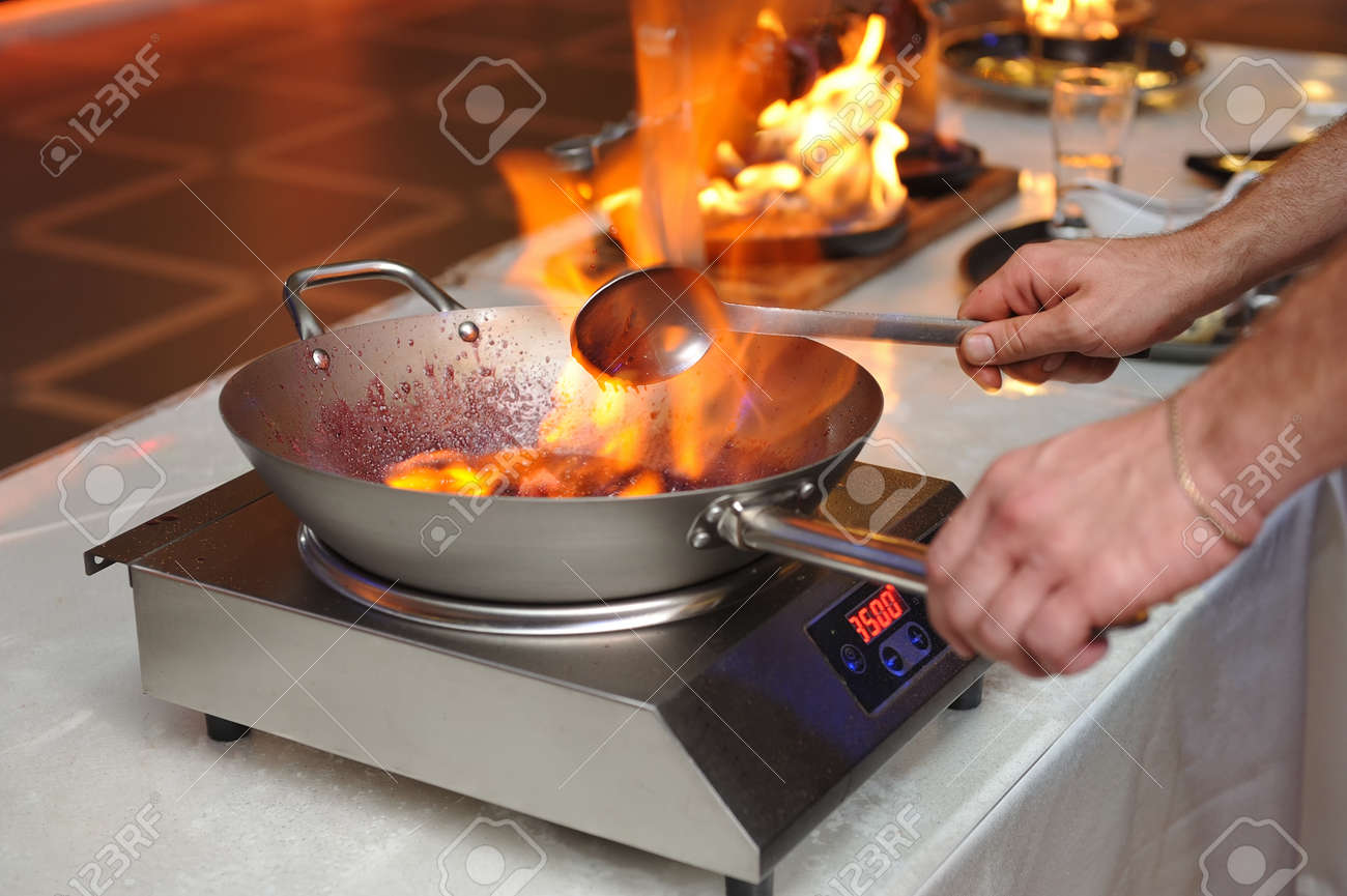 Cooking show the cook prepares food in a frying pan with fire stock photo