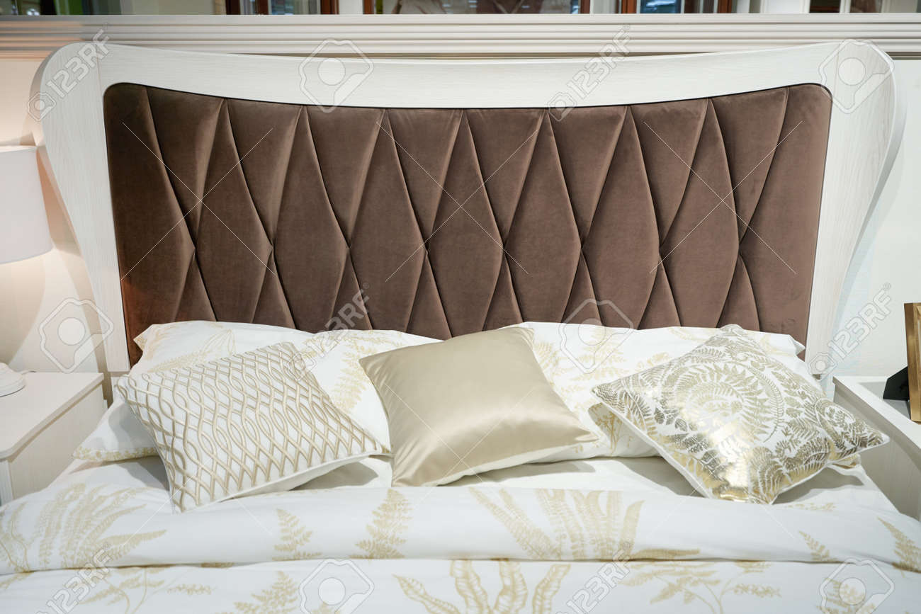 Bed With A Big Brown Soft Headboard And Pillows Stock Photo