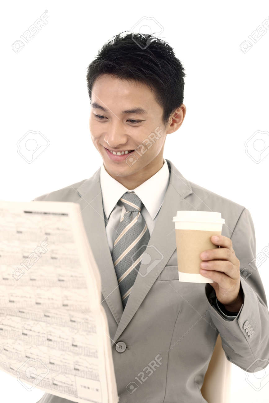 Businessman drinking coffee while reading newspaper Stock Photo - 4194321