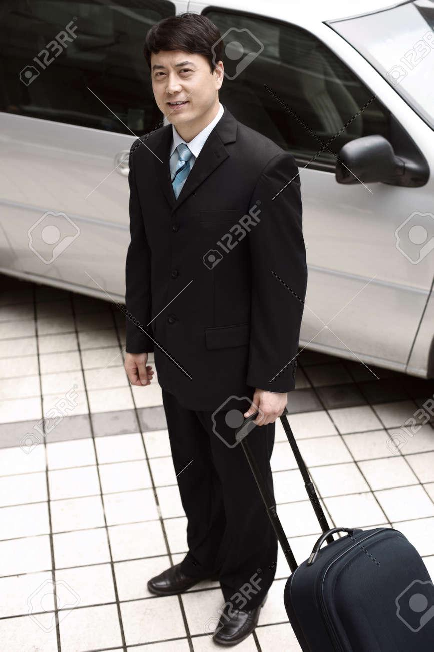 Businessman holding luggage next to car Stock Photo - 4194584