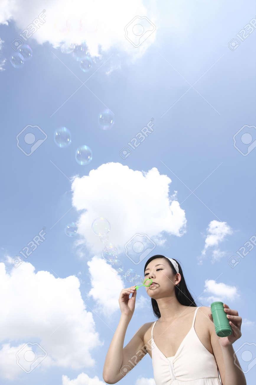 Woman blowing soap bubbles Stock Photo - 4197401