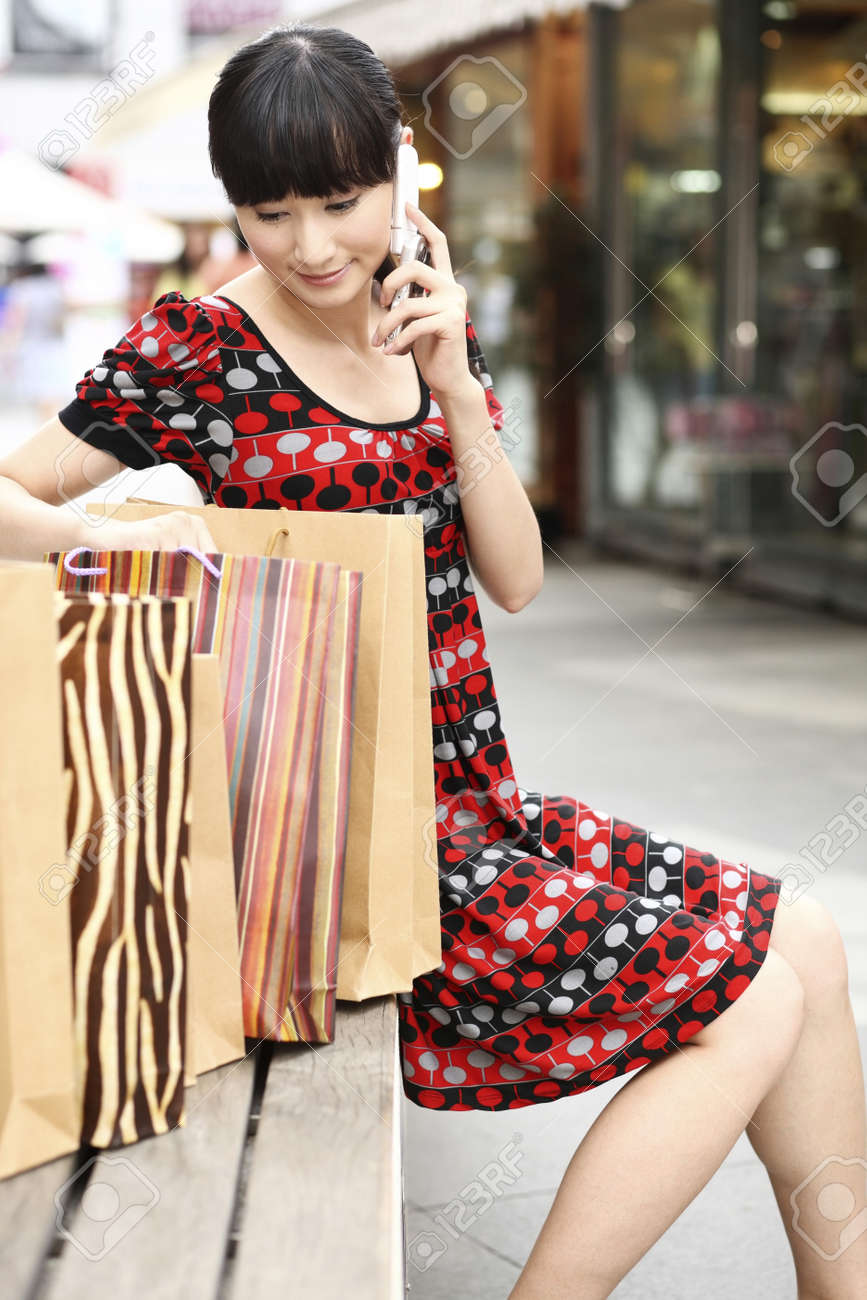 Woman looking into paperbag while talking on the phone Stock Photo - 4197645