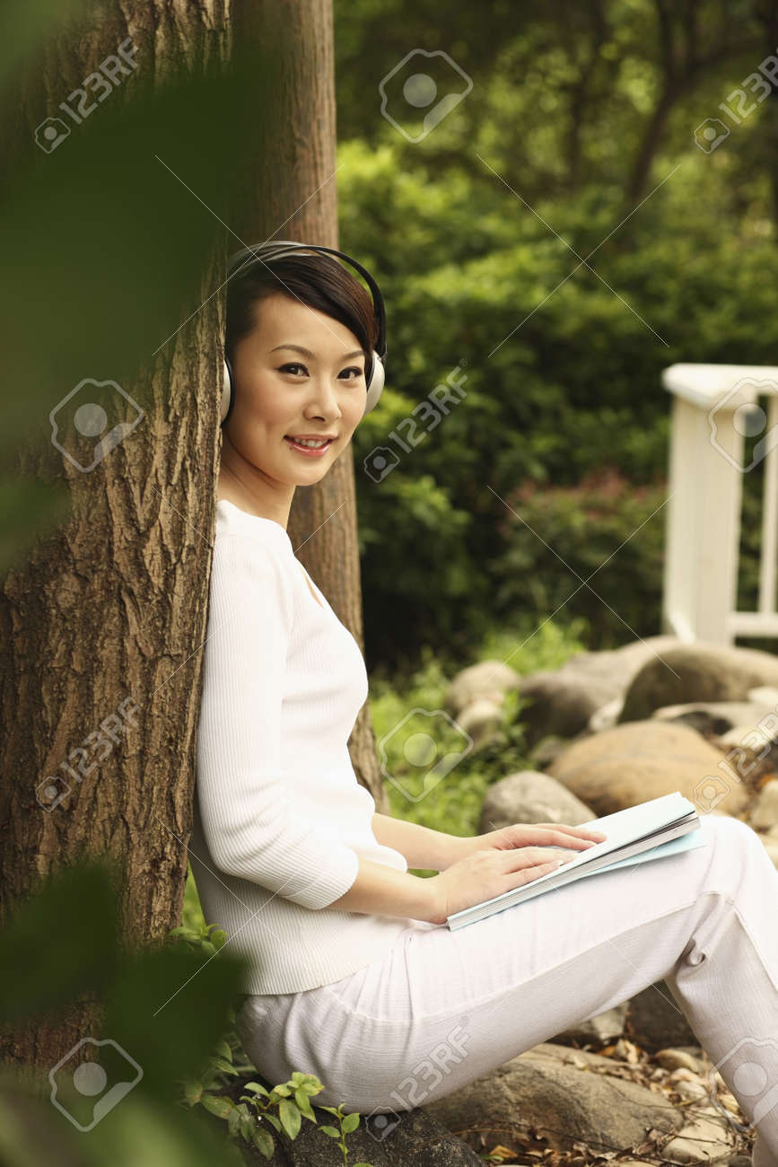 Woman leaning against tree, listening to music on the headphones Stock Photo - 4630234