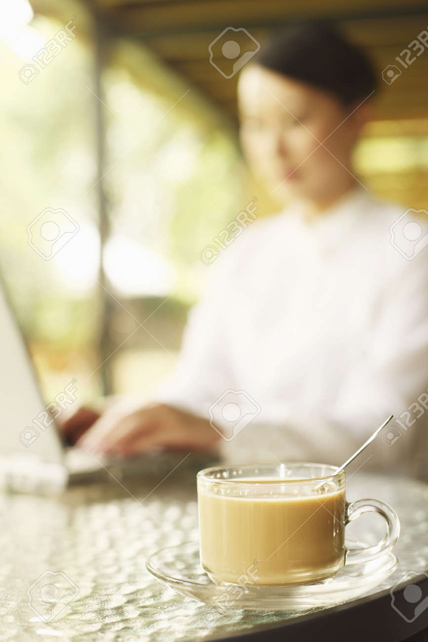 Focus on the cup of coffee, woman using laptop in the background Stock Photo - 4630266