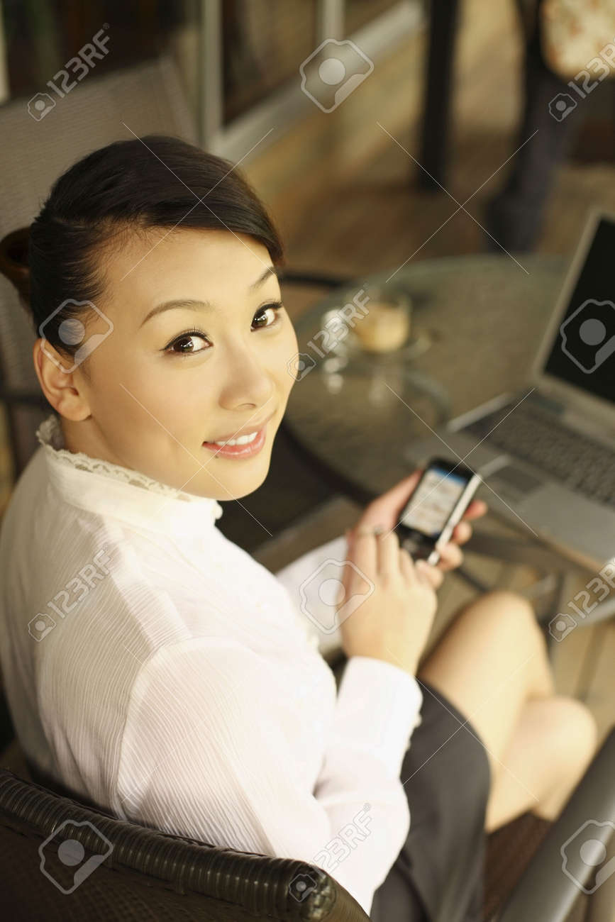 Woman holding PDA phone, smiling Stock Photo - 4630300