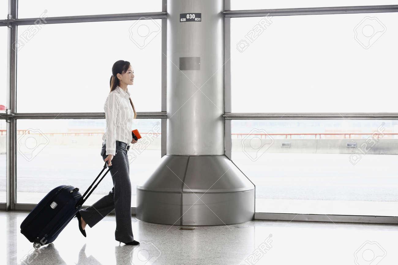 Woman walking through train station pulling suitcase Stock Photo - 4630201