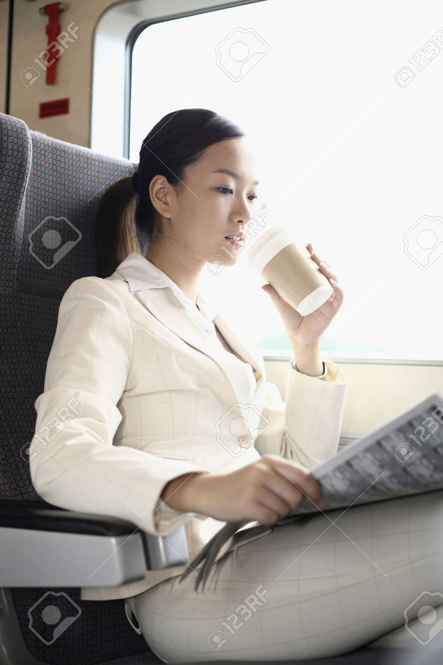 Woman reading newspaper and drinking coffee while traveling on the train Stock Photo - 4630303
