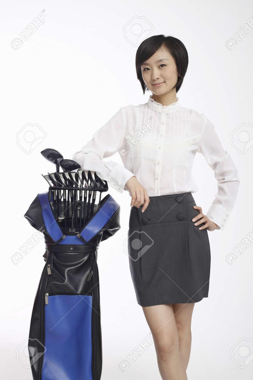 Woman posing beside golf bag Stock Photo - 4630763