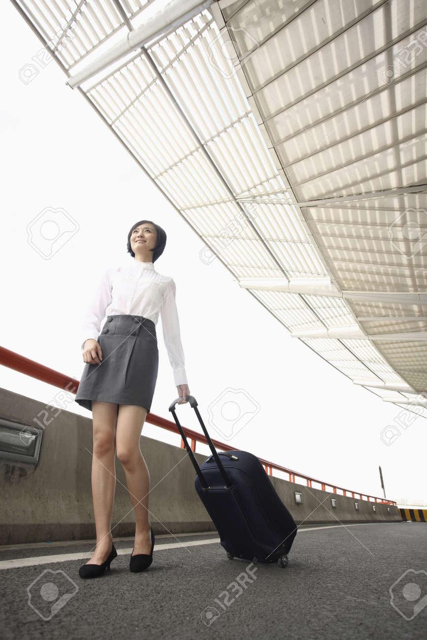 Woman walking through train station pulling suitcase Stock Photo - 4630725