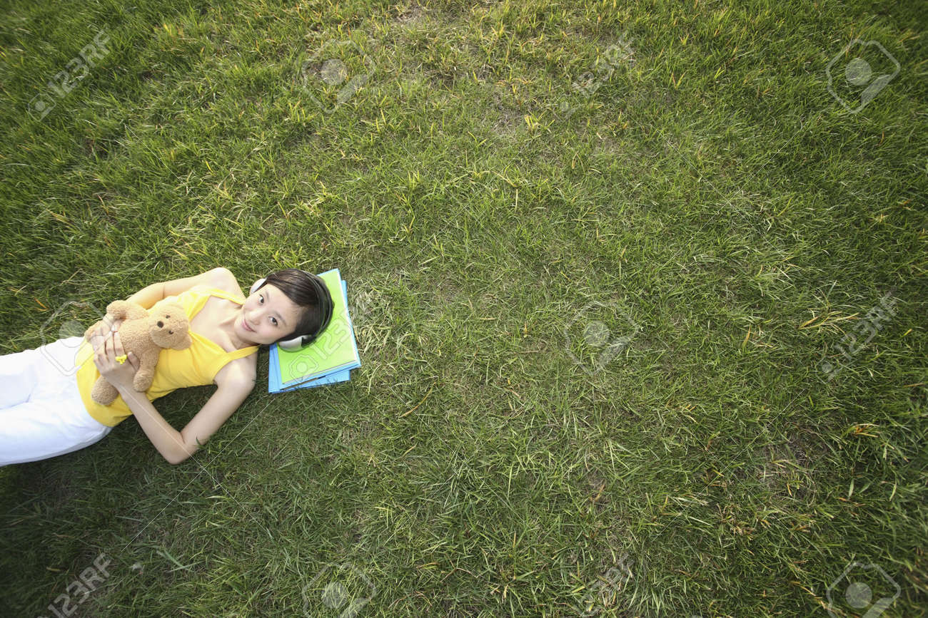 Woman with teddy bear lying on the grass listening to music Stock Photo - 4631047