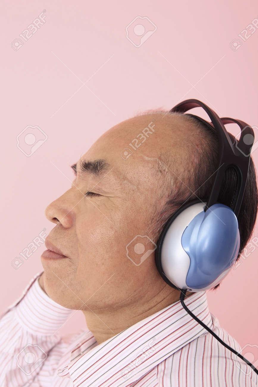 Senior man listening to headphones Stock Photo - 4636336