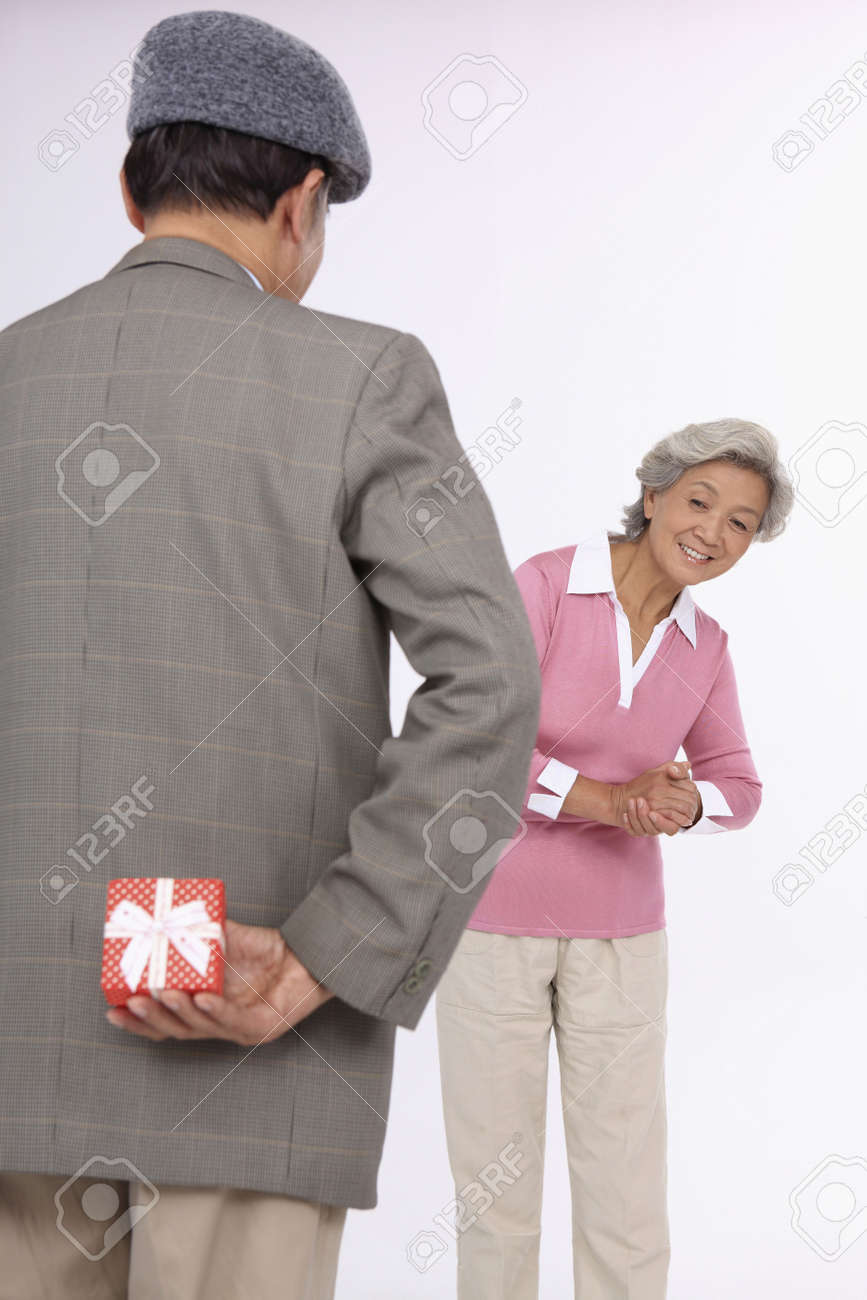 Senior man holding gift for senior woman behind his back Stock Photo - 4636414