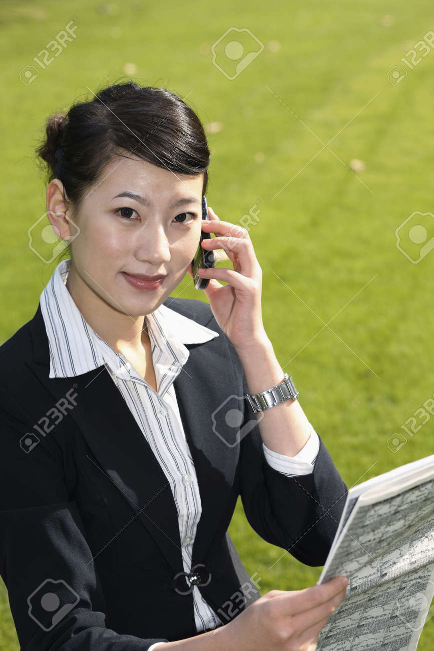 Businesswoman reading newspaper while talking on the phone Stock Photo - 4636394
