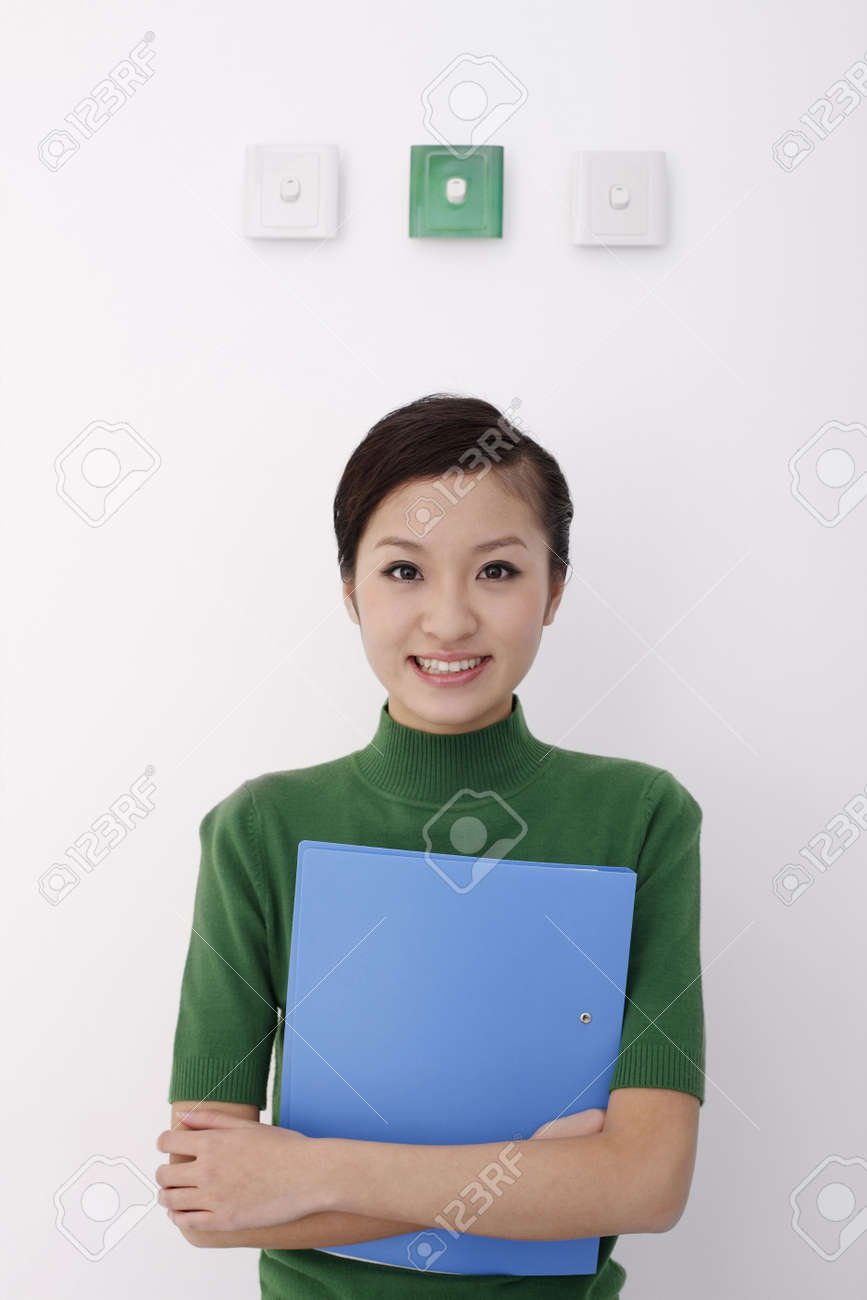 Woman holding file standing under light switches Stock Photo - 4653870