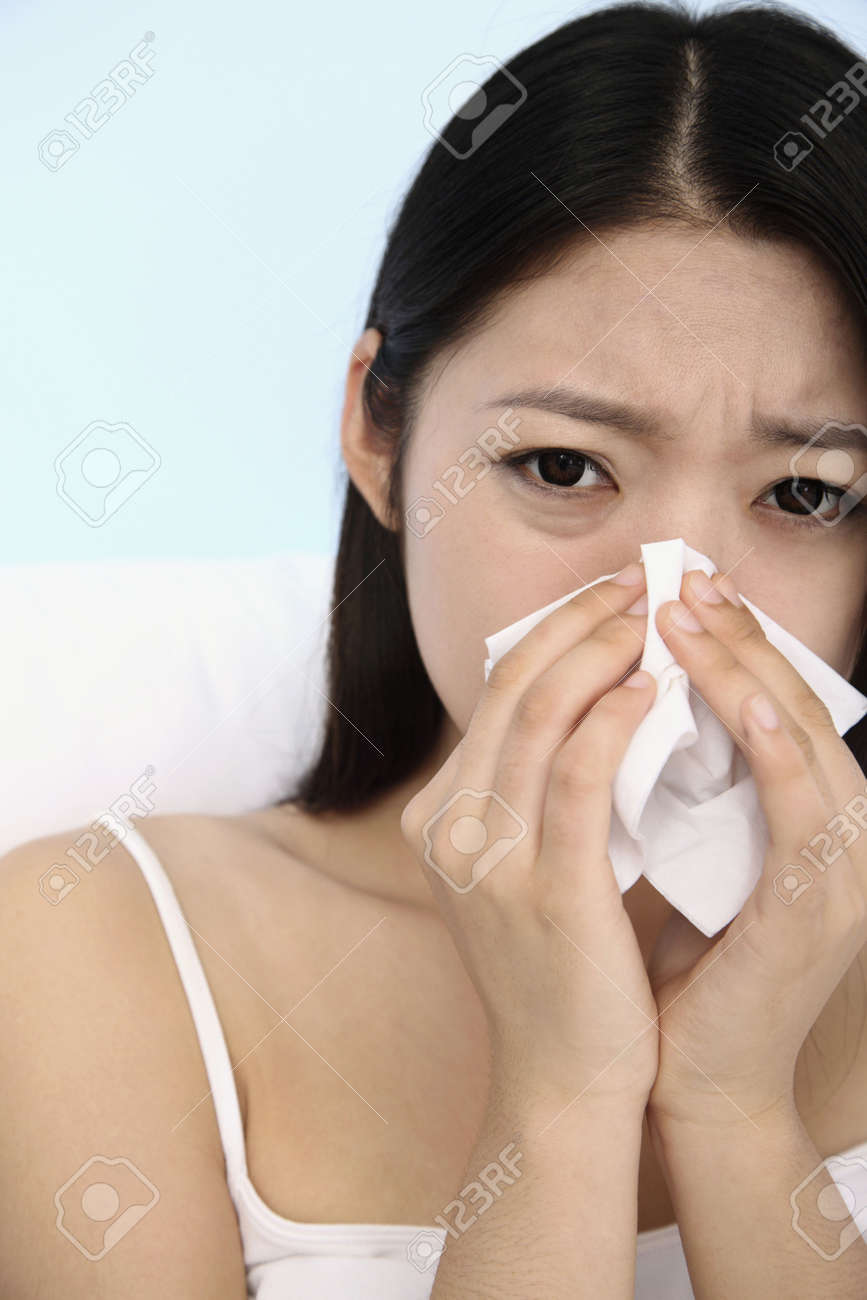 Woman blowing nose with tissue Stock Photo - 10294683