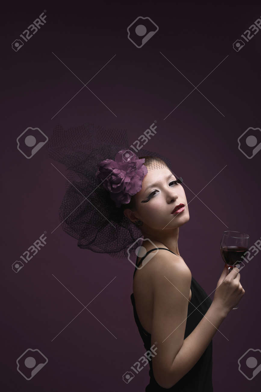 Woman with net and flower decorating her hair holding wine glass Stock Photo - 4778991