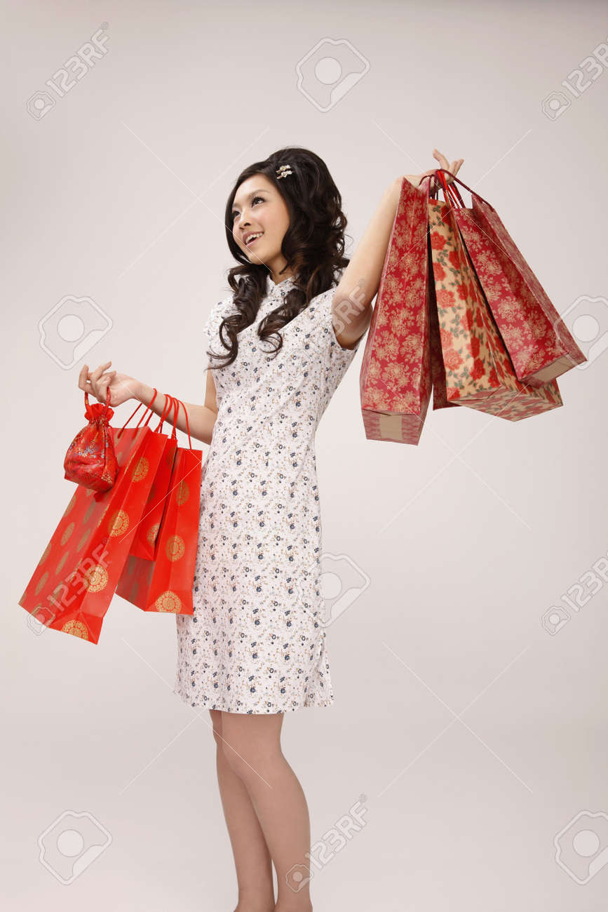 Woman in cheongsam carrying paperbags Stock Photo - 10294431