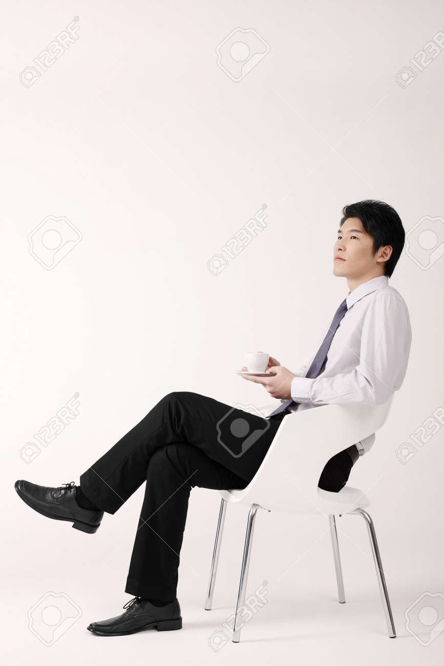 Man sitting in chair side - Man Relaxing On Chair Holding A Cup Of Coffee Stock Photo 4779688