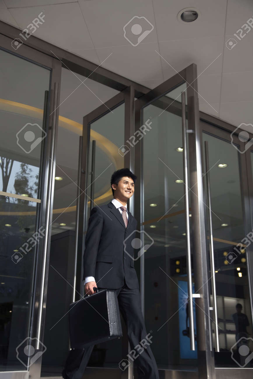 Businessman with briefcase walking out of a building Stock Photo - 4810725