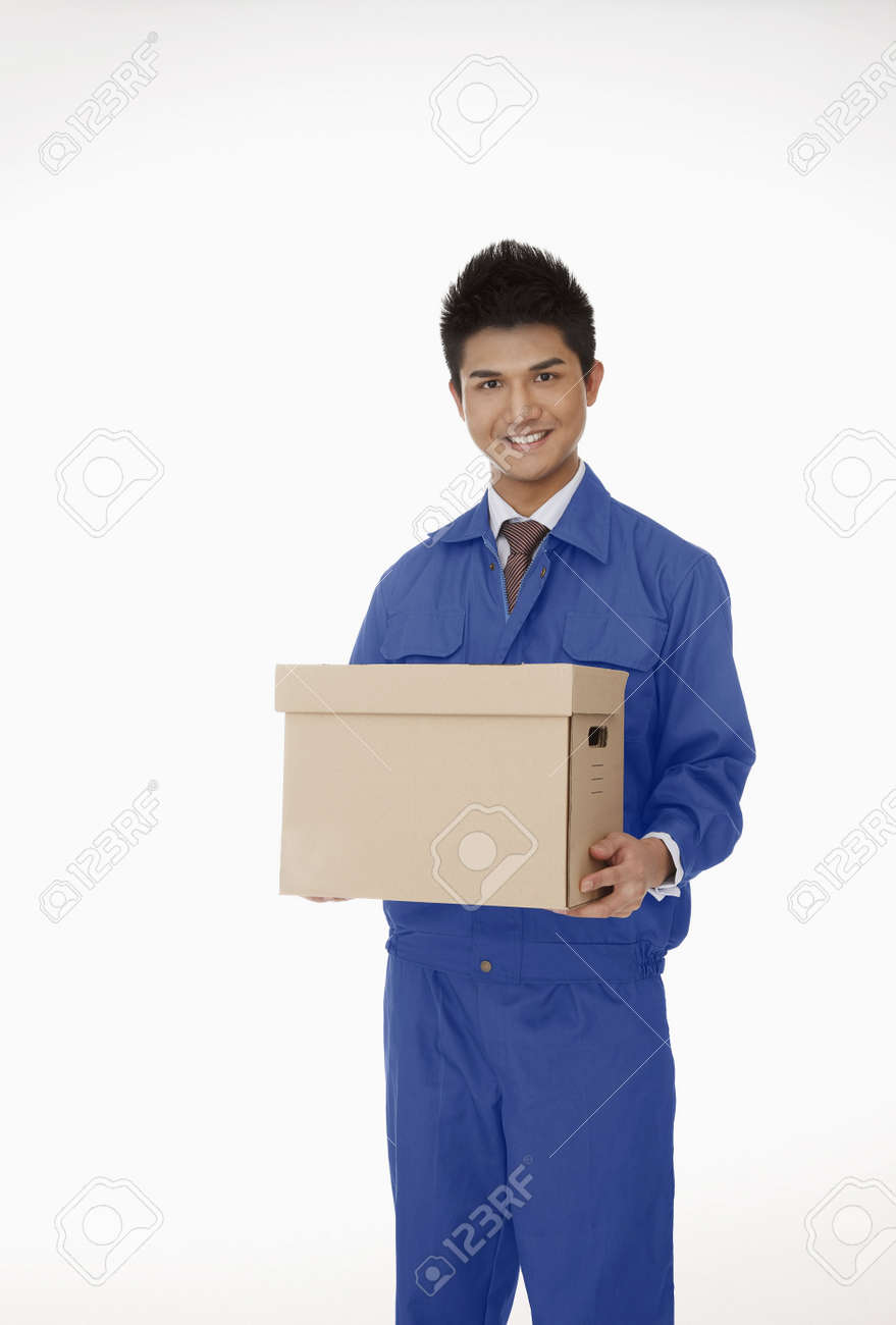 Businessman in protective workwear carrying a box Stock Photo - 4810479