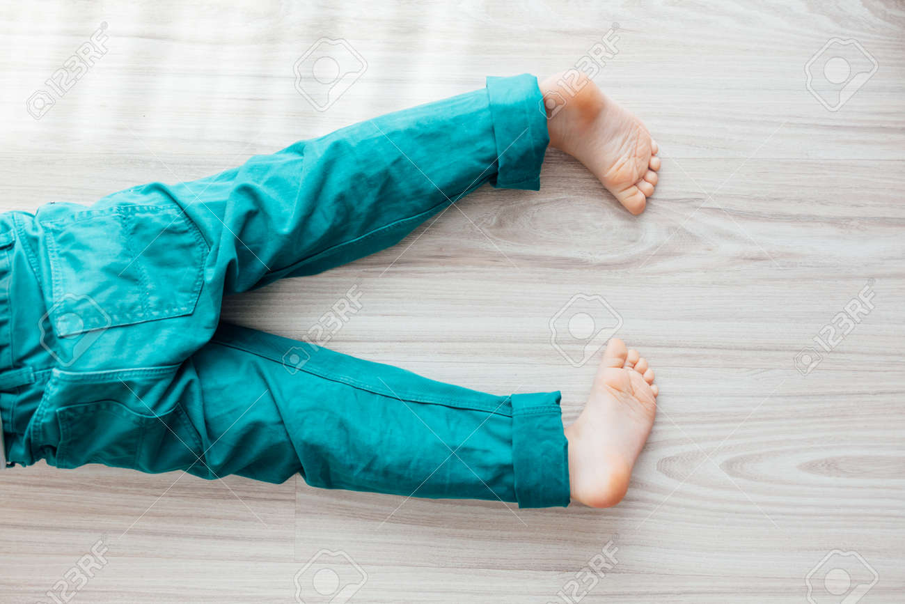 Closeup Of Young Barefoot Child With Turquoise Pants Laying Down On The Floor Stock Photo