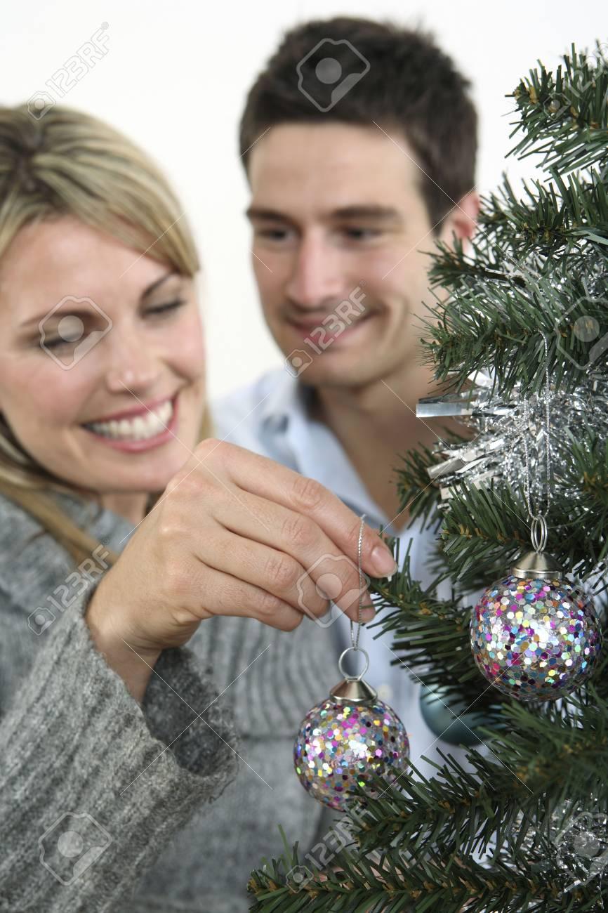 Woman hanging christmas bauble, man watching Stock Photo - 2966219