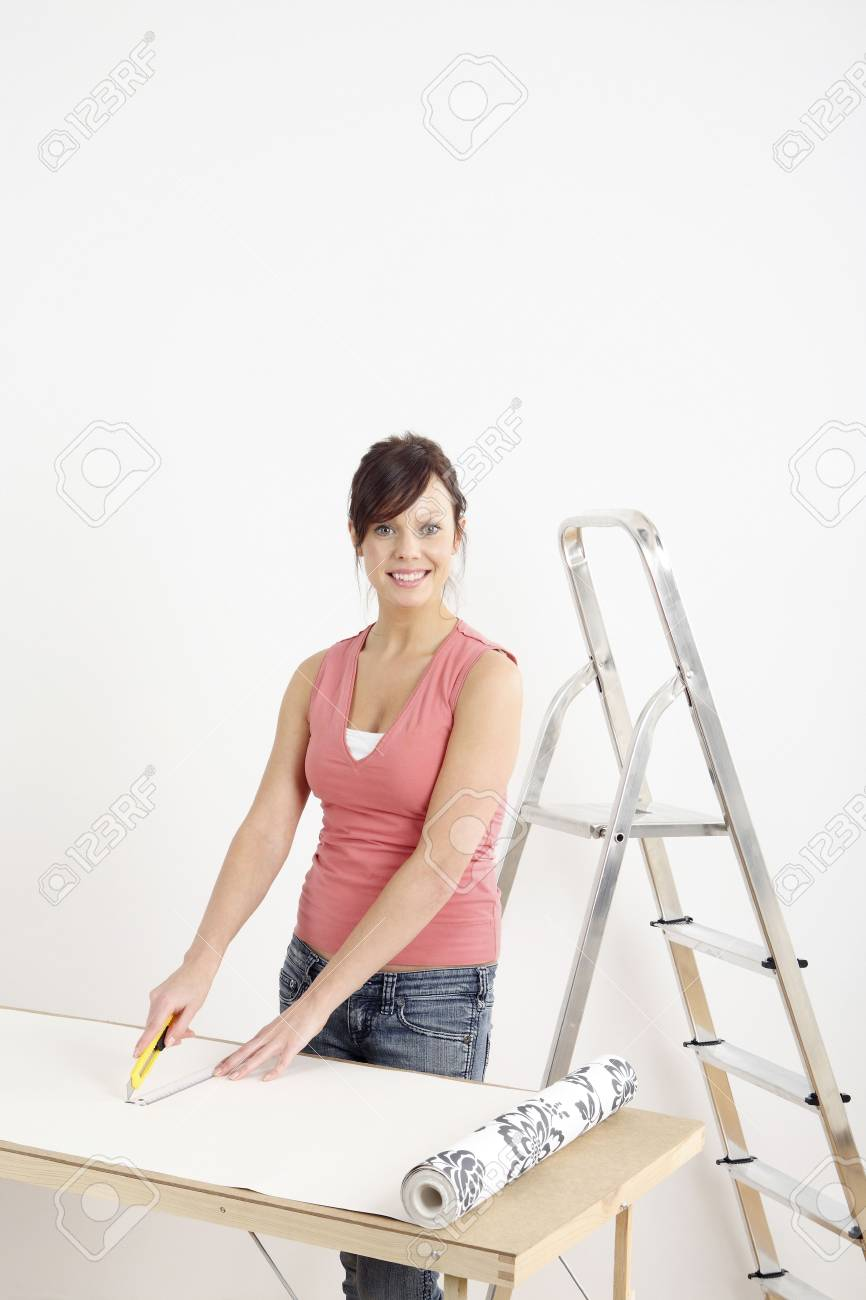 Woman cutting wallpaper Stock Photo - 2966429