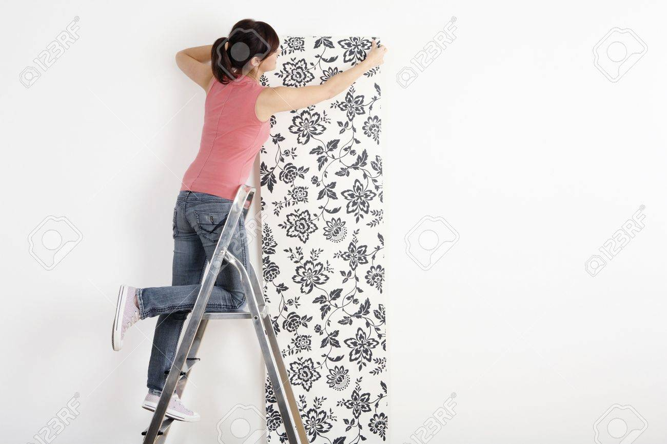 Woman decorating wall with wallpaper Stock Photo - 2966434