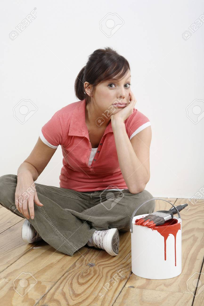 Woman sitting on the floor with a paint can and paintbrush beside her Stock Photo - 2966478