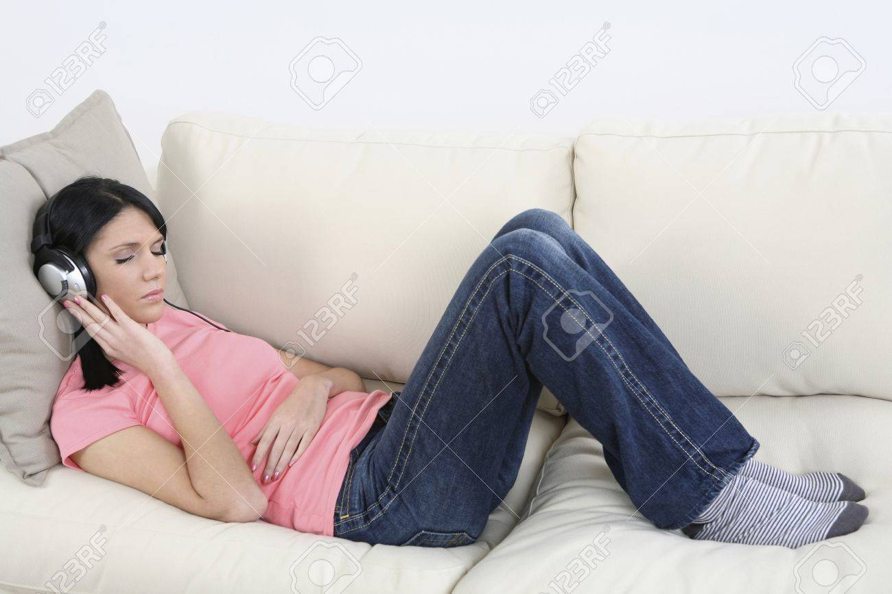 Woman lying down on the couch, listening to MP3 player with her eyes closed Stock Photo - 4099881