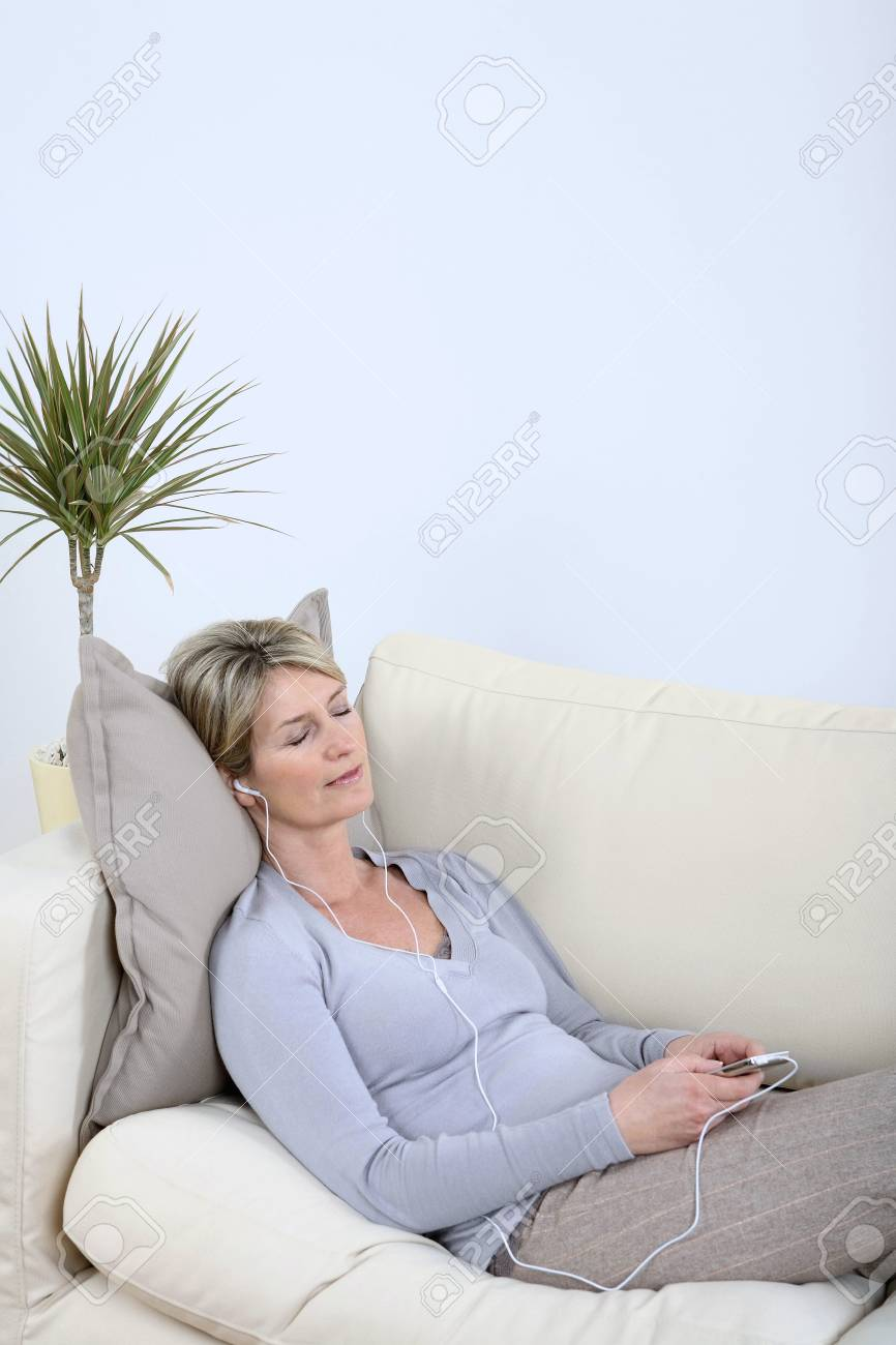 Woman lying on the couch, listening to music with her eyes closed Stock Photo - 4110905