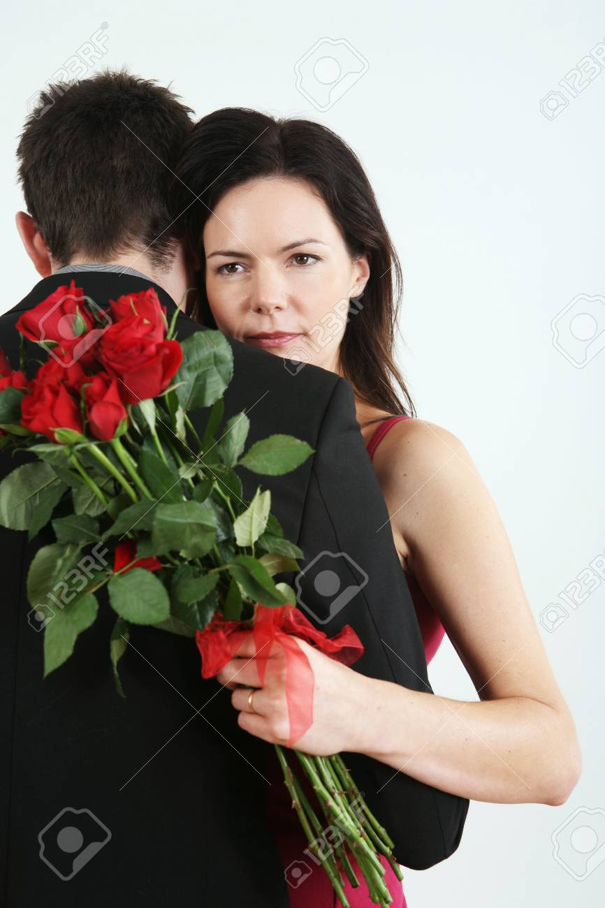 Man and woman embracing, woman holding bouquet of flowers Stock Photo - 4766967