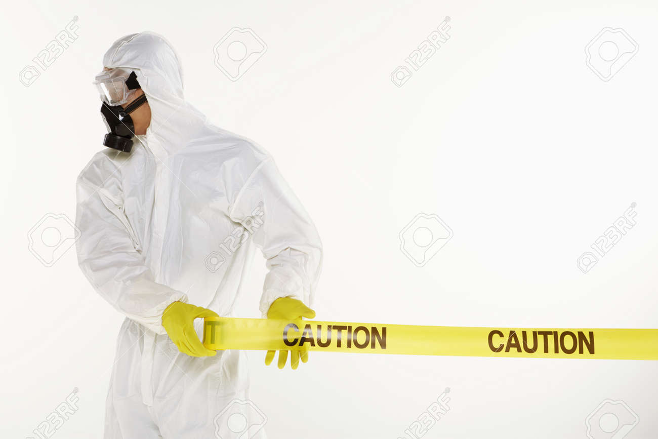 Man in protective suit rolling out the 'Caution' tape Stock Photo - 22844568