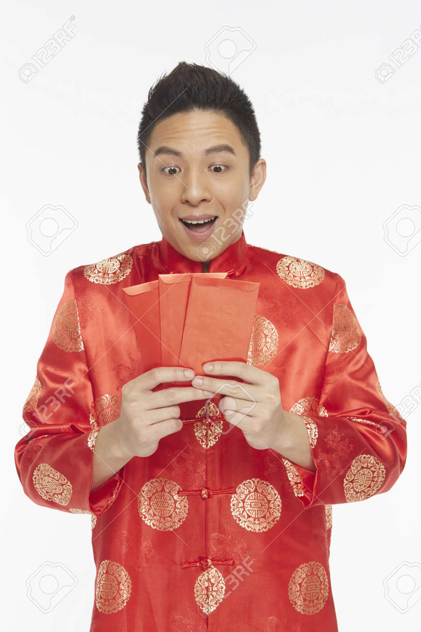 Man in traditional clothing holding up red packets Stock Photo - 22839242
