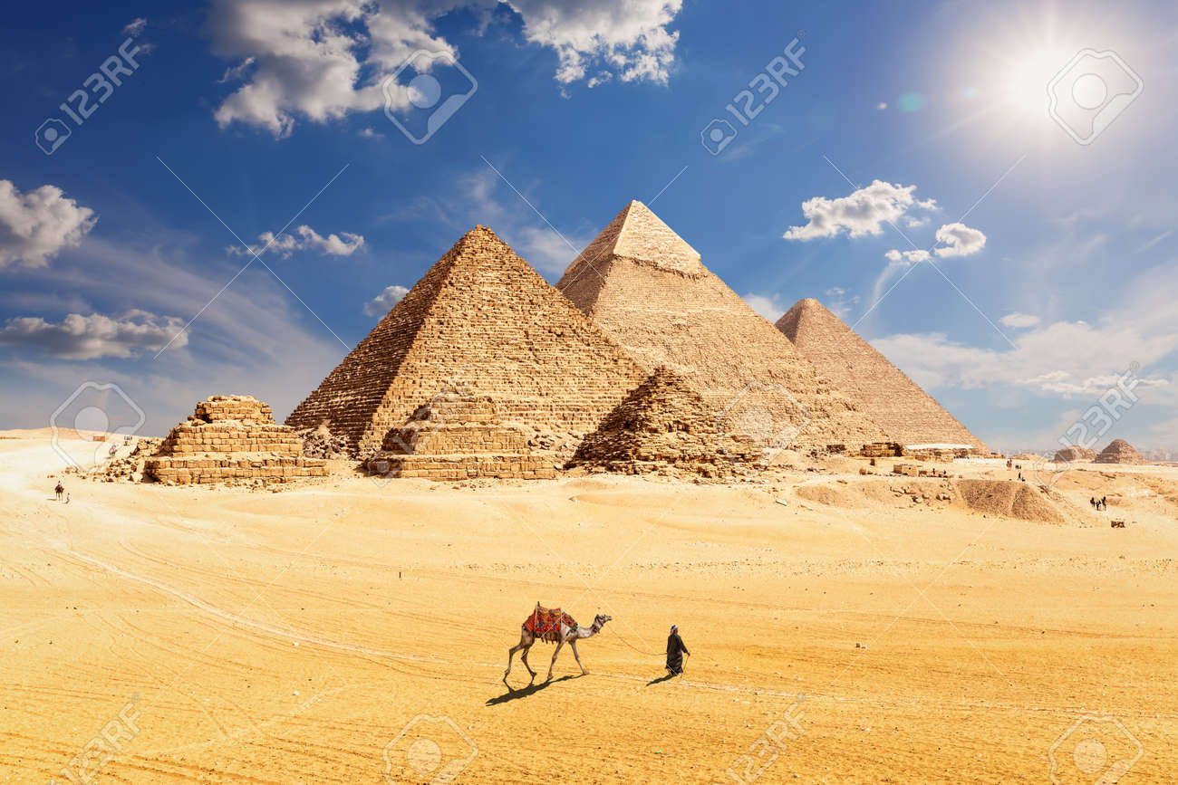 Famous Pyramids of Egypt and a bedouin with a camel, Giza, Cairo - 152809217