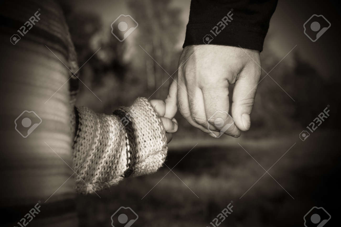A parent holding the hand of its child while walking in a park............ Stock Photo - 9078291