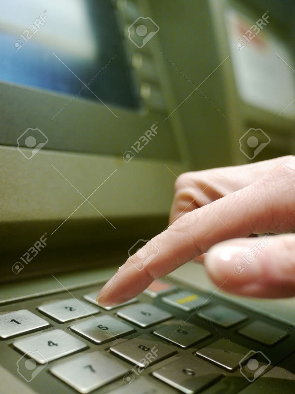 Finger using automatic teller keypad to enter pin number Stock Photo - 9143863