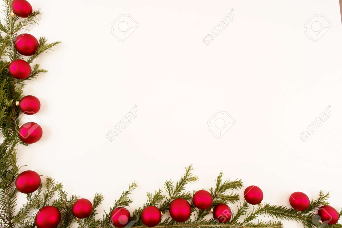 Border of red christmas garland with baubles and ribbons on white