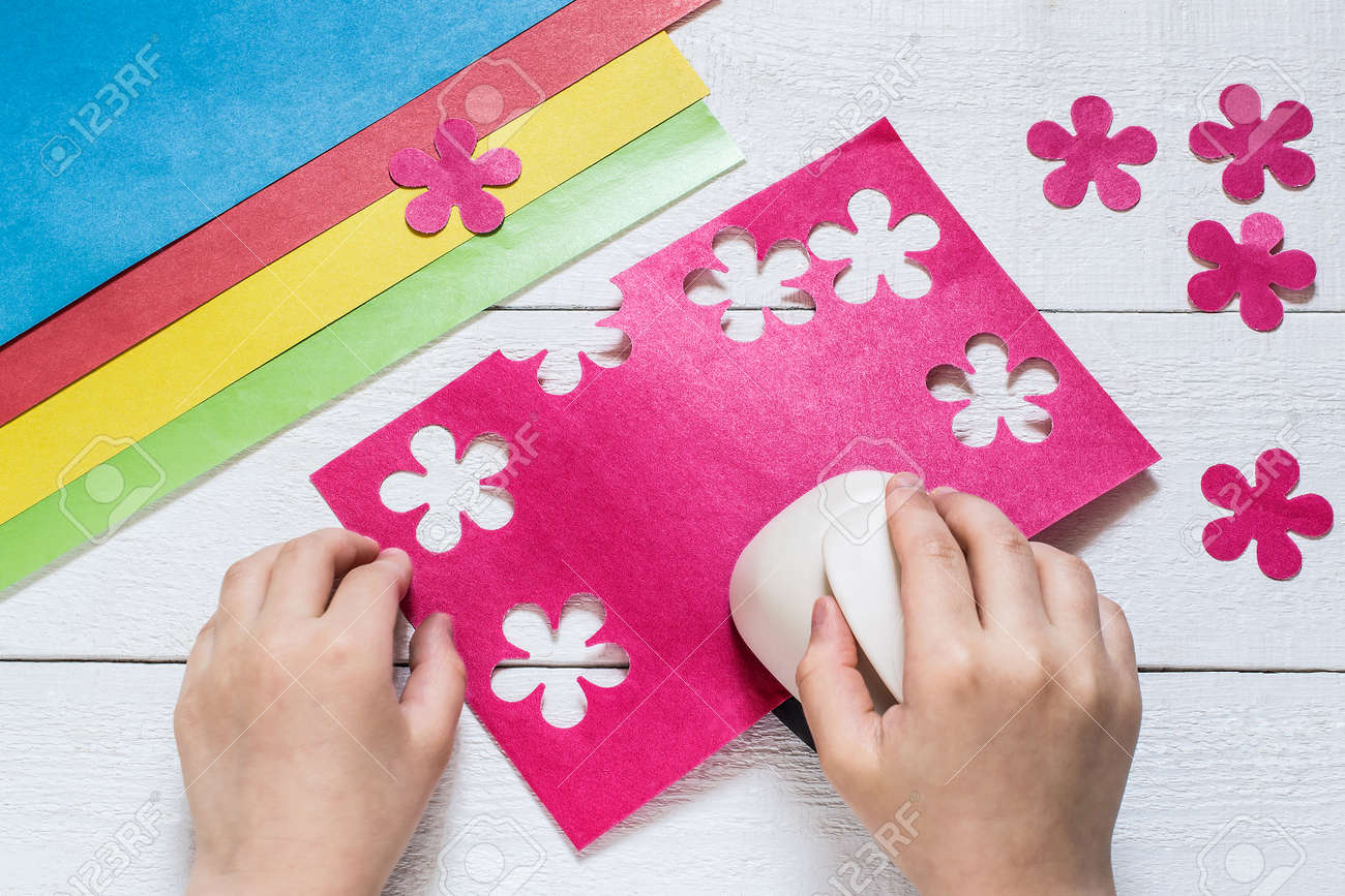 The Child Makes Special Hole Punch Flowers Of Pink Paper Sheets