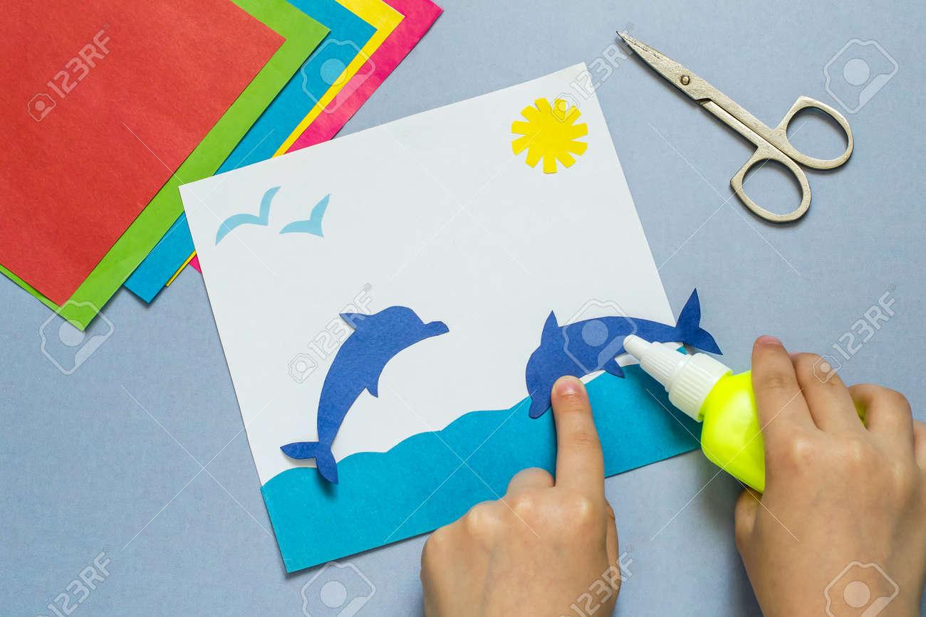 Immagini stock bambino incolla un delfino di carta rendendo il