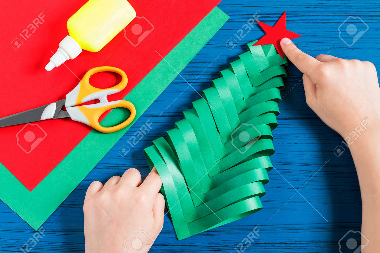 Making three,dimensional Christmas tree from paper to decorate..