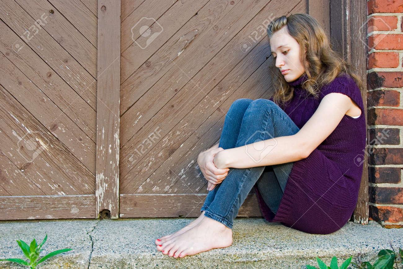 teenage girl huddled in old doorway Stock Photo - 10162093