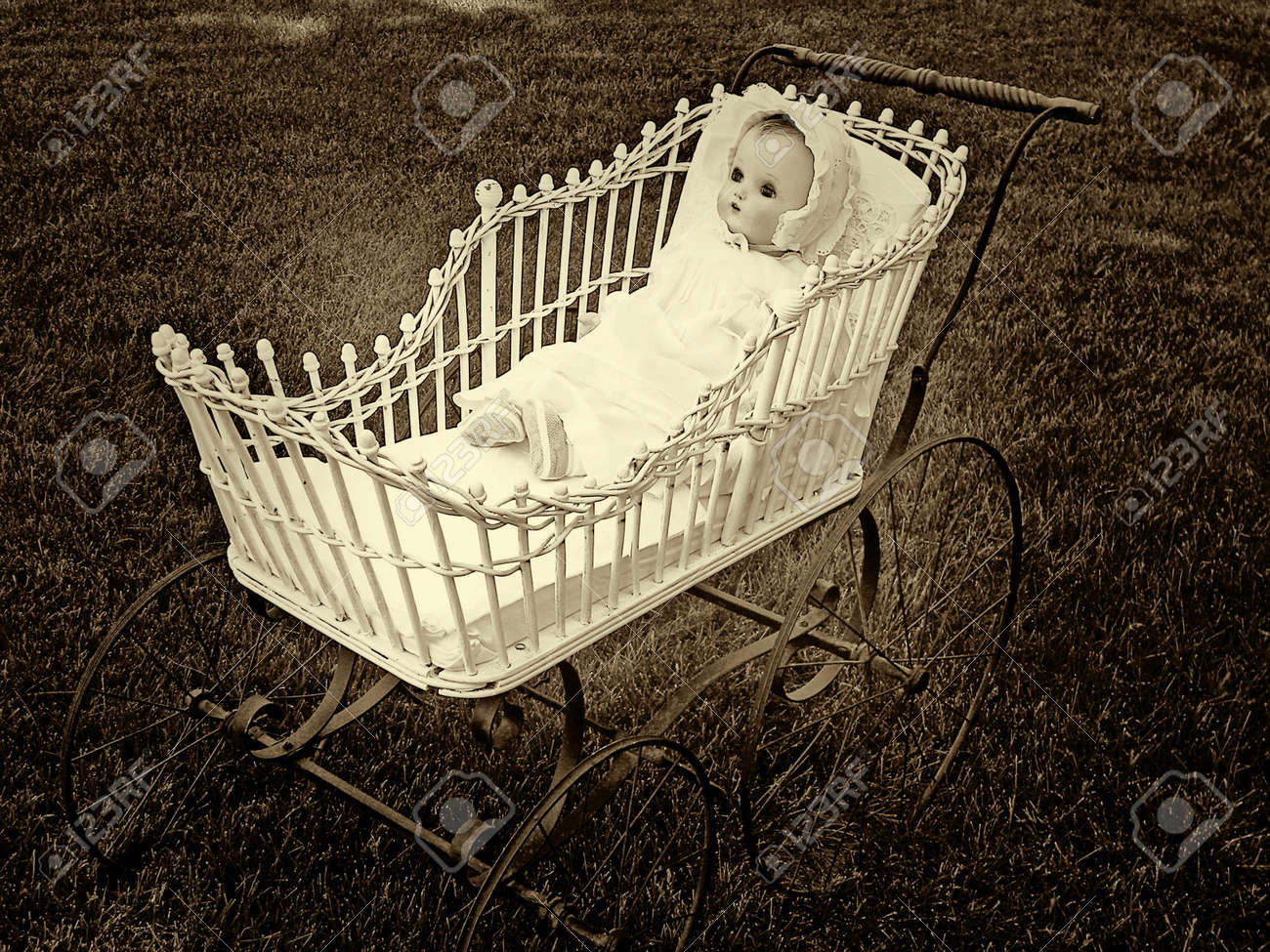 Vintage Doll In Old Fashioned Baby Buggy Sepia Stock Photo