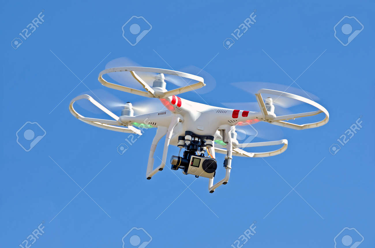 white drone hovering in bright blue sky Stock Photo - 38096715
