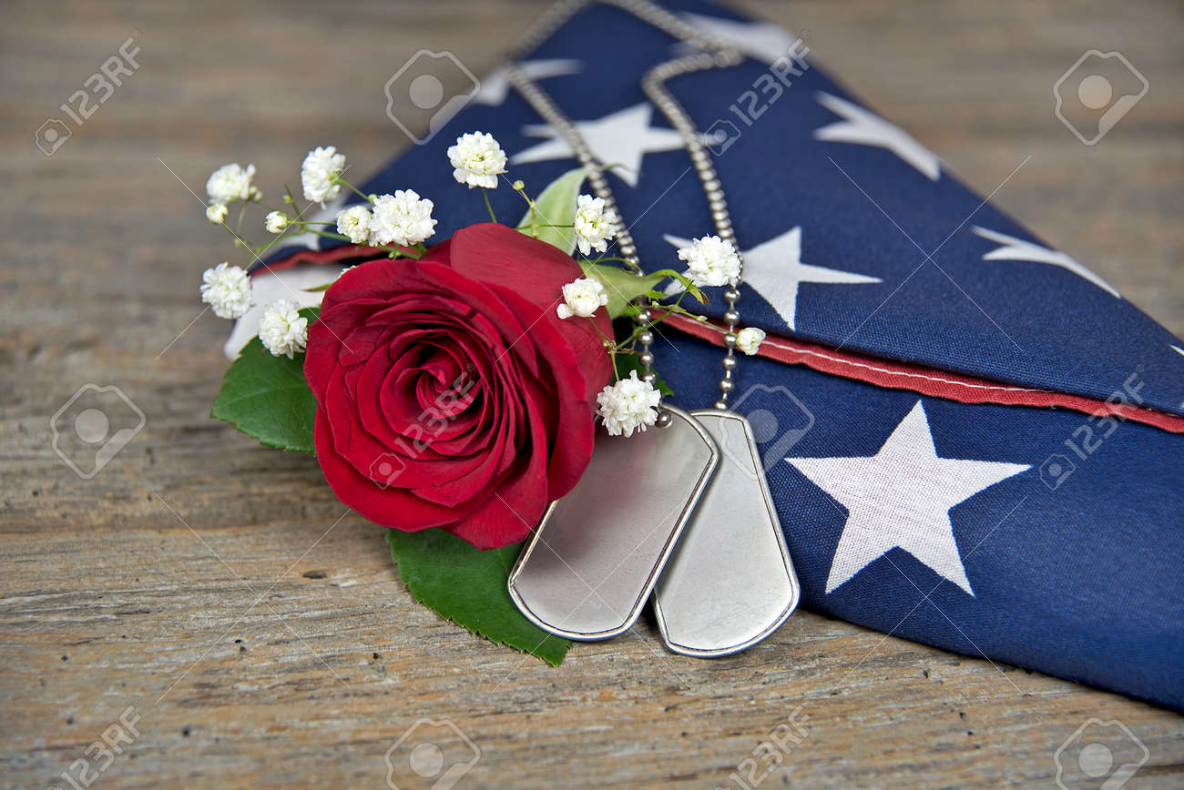 red rose and military dog tags on folded flag Stock Photo - 40954560