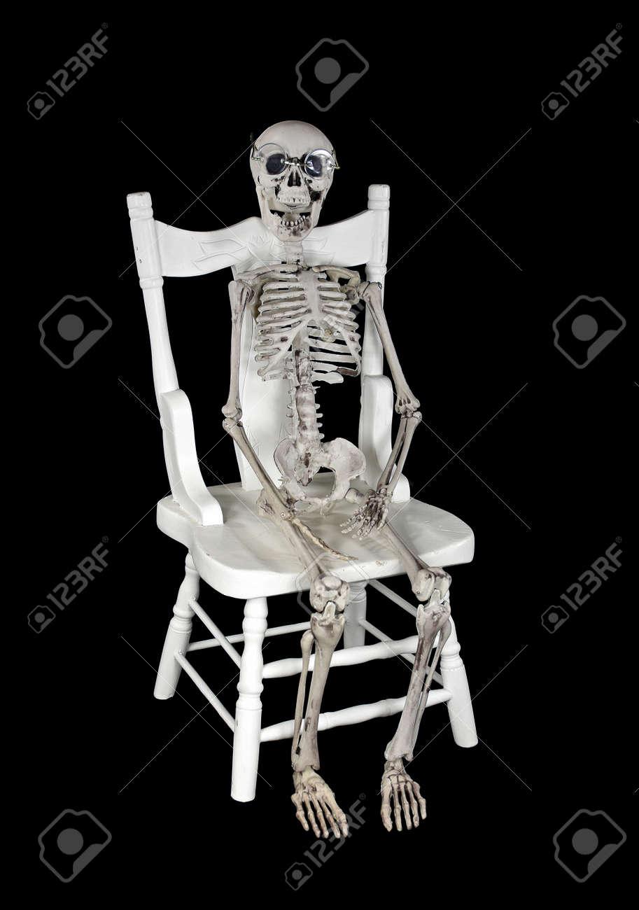 skeleton wearing glasses sitting on white wooden chair stock photo